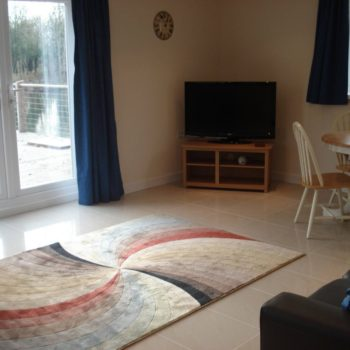 Living area with sofas, dining area and access to decking